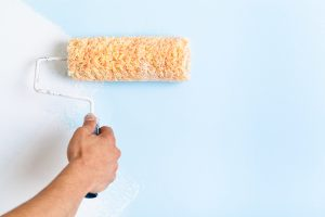 Close up of painter arm painting a wall with paint roller; copy space
